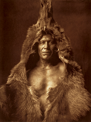 """Bear's Belly - Arikara""- 1904 Born in 1847 at Fort Clark in the present North Dakota. He had no experience in war when at the age of nineteen he joined Custer's scouts at Fort Abraham Lincoln, having been told by old men of the tribe that such a course was the surest way to gain honors. Shortly after his arrival, Custer led a force into the Black Hills country; in the course of which, the young Arikara counted two first coups and one second. Bear's Belly fasted once. Going to an old man for advice, he was taken to the outskirts of the village to an old buffalo skull, commanded to strip, smear his body with white clay, and sit in front of the skull. When he had taken the assigned position, the old man held up a large knife and an awl while he addressed the buffalo skull: ""this young man sits in front of you, and is going to endure great suffering. Look upon him with great favor, you and Neshanu, and give him a long, prosperous life."" With that he cut pieces of skin from the faster's breast and held them out to the buffalo skull. Bear's Belly married at the age of nineteen. He became a member of the Bears in the medicine fraternity and relates the following story of an occurrence connected with that event: ""Needing a bearskin in my medicine-making, I went, at the season when the leaves were turning brown, into the White-Clay hills. All the thought of my heart that day was to see a bear and kill him. I passed an eagle trap, but did not stop: it was a bear I wanted, not an eagle. Coming suddenly to the brink of a cliff I saw me three bears. My heart wished to go two ways: I wanted a bear. But to fight three was hard. I decided to try it, and, descending, crept up to within forty yards of them, where I stopped to look around for a way of escape if they charged me. The only way out was by the cliff, and as I could not climb well in moccasins I removed them. One bear was standing with his side toward me, another was walking slowly toward him on the other side. I waited until the second one was close to the first and pulled the trigger. The farther one fell; the bullet had passed through the body of one and into the brain of the other. The wounded one charged, and I ran, loading my rifle, then turned and shot again, breaking his backbone. He lay there on the ground only ten paces from me and I see his face twitching. A noise caused me to remember the third bear, which I saw rushing upon me only six or seven paces away, I was yelling to keep up my courage and the bear was growling in his anger. He rose on his hind legs, and I shot, with my gun nearly touching his chest. He gave a howl and ran off. The bear with the broken back was dragging himself about with his forelegs, and I went to him and said, 'I came looking for you to be my friend, to be with me always.' Then I reloaded my gun and shot him through the head. His skin I kept, but the other two I sold."""